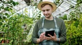 портативный : Slow motion of handsome young man in apron using tablet in glasshouse working alone with modern device touching screen. Farming and technology concept.