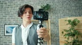 デバイス : Creative student stylish boy is recording video holding camera talking gesturing at home in loft style room. Blogging, apartment and young people concept. 動画素材