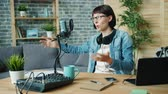 デバイス : Emotional young woman is speaking gesturing recording audio in microphone at home using modern equipment. People, youth lifestyle and technology concept. 動画素材