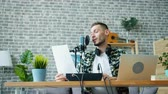 mass media : Joyful bearded guy is reading in microphone holding paper making podcast in studio enjoying occupation. Happy people, communication and blogging concept. Filmati Stock