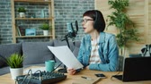şair : Portrait of creative young lady recording podcast in microphone speaking holding paper with speech working at home alone. People and modern lifestyle concept. Stok Video
