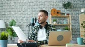 live stream : Good-looking guy is reading information in microphone talking making podcast in studio sitting at desk alone. Blogging, communication and people concept. Stock Footage