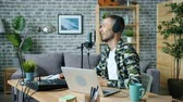 デバイス : Joyful guy is talking in microphone wearing headphones using laptop in studio sitting at desk alone creating podcast. Modern mass media and equipment concept. 動画素材