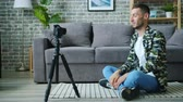 デバイス : Handsome young man blogger is recording video for internet vlog talking smiling using camera on tripod sitting on floor in studio apartment. People and lifestyle concept.