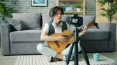 デバイス : Slow motion of cheerful teenage blogger boy talking for camera holding guitar sitting on floor at home. Creative youth, apartment and blogging concept. 動画素材