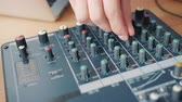 デバイス : Close-up shot of male hand adjusting sound using modern audio equipment on table in recording studio. Contemporary technology, people and electronics concept.