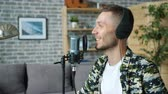 live stream : Slow motion of happy young man in headphones talking in microphone in recording studio smiling enjoying communication. Podcasts and audio blogging concept.