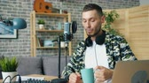 デバイス : Cheerful young man is enjoying coffee and recording podcast audio in modern studio talking in microphone. Laptop and headphones are visible in workplace.