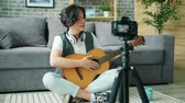 tutoriel : Creative boy teenager recording tutorial about guitar for online vlog talking for camera holding musical instrument touching strings. Childhood and blogging concept.