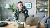 live stream : Slow motion of young adult man recording podcast for audio blog using mic and laptop working at table at home. Blogging, equipment and apartment concept. Stock Footage