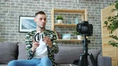 デバイス : Gadget expert young man is recording video about wireless headphones talking holding device showing for camera at home. People and advertisement concept.