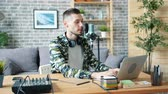 mass media : Handsome guy is using professional microphone and laptop talking recording podcart in apartment enjoying occupation. Bloggers and modern technology concept.