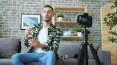 デバイス : Popular blogger handsome guy is advertising modern watch recording video talking for camera holding device sitting on couch. Advertisement and blogging concept. 動画素材