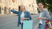 kifinomult : Smiling mature women friends with shopping bags are hailing taxi waving hand outdoors in city street on summer day. Business, people and transport concept. Stock mozgókép