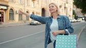kifinomult : Attractive mature woman with shopping bags is waving down taxi in city street smiling gesturing waiting for cab. Transportation, lifestyle and emotions concept. Stock mozgókép