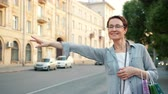 kroupy : Beautiful mature brunette with shopping bags is hailing taxi downtown in city street waving hand smiling standing alone. People and transportation concept.