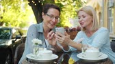 デバイス : Happy ladies friends are laughing chatting looking at smart phone screen sitting in outdoor cafe together enjoying modern technology. Emotions and gadgets concept.