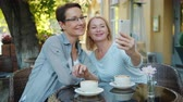 デバイス : Beautiful mature women friends are taking selfie with smartphone camera and talking posing in outdoor cafe. Photograph, people and modern lifestyle concept.