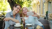 デバイス : Mature blonde is taking selfie with female friend in outdoor cafe holding coffee cup posing using smartphone. Photograph, lifestyle and friendship concept.