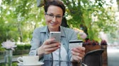 купить : Joyful mature woman with short hair is paying with credit card using smartphone outdoors in street cafe. Modern technology, consumerism and shopping concept.