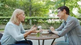 fofoca : Mature lady is talking to female friend in open air cafe having fun laughing sitting at table together. Conversation, people and modern lifestyle concept. Vídeos