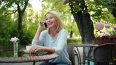 kifinomult : Happy mature woman talking on mobile phone laughing sitting on street cafe outdoors enjoying communication. Lifestyle, modern devices and happiness concept. Stock mozgókép