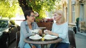 kifinomult : Attractive ladies happy friends are chatting in outdoor cafe holding coffee cups smiling relaxing on summer day. Happiness, drinks and lunch break concept. Stock mozgókép