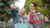 デバイス : Beautiful mature women friends are taking selfie with smartphone camera posing with bright shopping bags outdoors. Modern technology and photograph concept. 動画素材