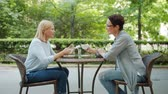thee : Beautiful middle-aged women friends are chatting holding coffee cups in outdoor cafe in summer enjoying warm day outside. People and relaxation concept.
