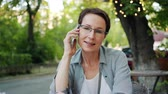 デバイス : Mature woman in glasses is talking on mobile phone enjoying conversation smiling sitting in open air cafe outdoors. Conversation, emotions and people concept.