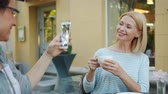 デバイス : Friend woman is taking photo of beautiful mature blonde holding coffee cup in street cafe smiling posing. Modern technology, people and leisure concept. 動画素材