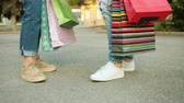 купить : Low angle shot of womens legs standing in the street with colorful paper bags after busy day in shops. People, leisure, shopping and friendship conccept.