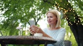 デバイス : Attractive mature blonde in casual clothing is using smartphone enjoying summer day in open air cafe. Modern technology, people and leisure time concept.