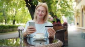 купить : Mature lady is paying with bank card using smartphone touching screen and smiling relaxing in street cafe alone. Inernet shopping and payment concept. Стоковые видеозаписи