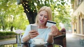 купить : Cheerful woman is paying with credit card online in internet shop entering bank card information in outdoor cafe. Modern technology and shopping concept.