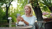 デバイス : Good-looking mature lady enjoying smartphone touching screen in street cafe sitting at table alone using device. People, lifestyle and gadgets concept.