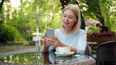 kifinomult : Slow motion of happy mature woman using smartphone touching screen relaxing in outside cafe in summer. People, devices and modern technology concept. Stock mozgókép