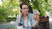 デバイス : Pretty mature lady is taking selfie with smartphone camera posing relaxing sitting in outdoor cafe alone. Photography, modern devices and lifestyle concept.