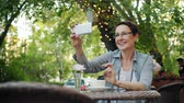 chatten : Mature lady in glasses is making online video call relaxing in street cafe in city sitting at table alone talking holding smartphone. Conversation and internet concept. Stock Footage
