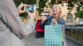 デバイス : Happy shopaholic mature lady is posing for smartphone camera holding shopping bags outdoors while friend taking picture. Photography and consumerism concept. 動画素材