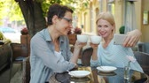 デバイス : Mature ladies friends are taking selfie with cups in open air cafe holding coffee smiling posing for smartphone camera having fun. People and drinks concept. 動画素材