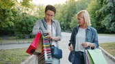 kifinomult : Beautiful women are walking in the street with paper bags and talking on autumn day in city. Shopping together, friendship and enjoyable leisure concept.