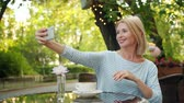 デバイス : Cheerful lady is taking selfie with smartphone camera posing in outdoor cafe alone having fun with modern device. Photograph, happiness and lifestyle concept.