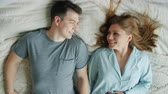 pyjama : Slow motion of young loving couple husband and wife falling on bed smiling relaxing enjoying romantic relationship at home. People and lifestyle concept. Stockvideo