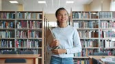 prateleira de livros : Cheerful teenage girl in casual clothing is walking with books in high school library smiling looking around. Modern education, people and lifestyle concept.