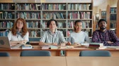 könyvtár : Portrait of cheerful young people students sitting in college library together smiling looking at camera. Education, happy people and lifestyle concept. Stock mozgókép
