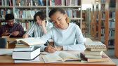 teenage boys : Tired African American girl diligent student is studying in college library writing reading books feeling exhausted. People, emotions and education concept.