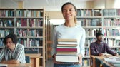 ansiklopedi : Pretty mixed race lady student is carrying books walking in library smiling while people studying reading at tables. Youth, education and literature concept. Stok Video