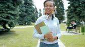 middelbare school : Pretty African American girl student is walking outdoors in park holding books smiling looking around at lawns and trees. Lifestyle, nature and people concept.