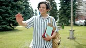 hélio : Cheerful guy student is walking outdoors in park waving hand greeting friends holding books smiling looking around. Happy people and lifestyle concept.